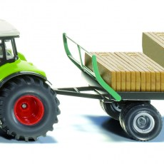 Claas tractor met balengrijper en aanhanger